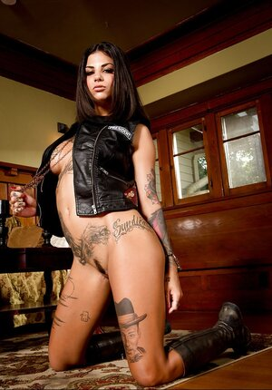 Impressive inked model poses absolutely naked dressed only in leather jacket